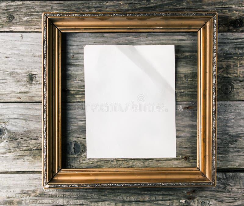 Vintage frame with paper on old wooden background. Vintage golden frame witn crumpled blank paper on old wooden background royalty free stock photos