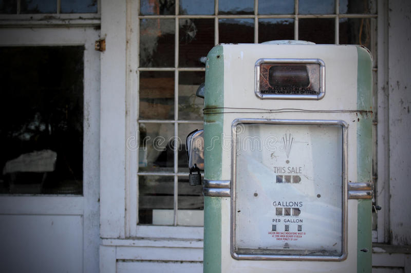 Vintage fuel pump. A vintage fuel pump in front of a wall of windows of an abandoned gas station. Shallow depth of field. Aging of picture effects royalty free stock images