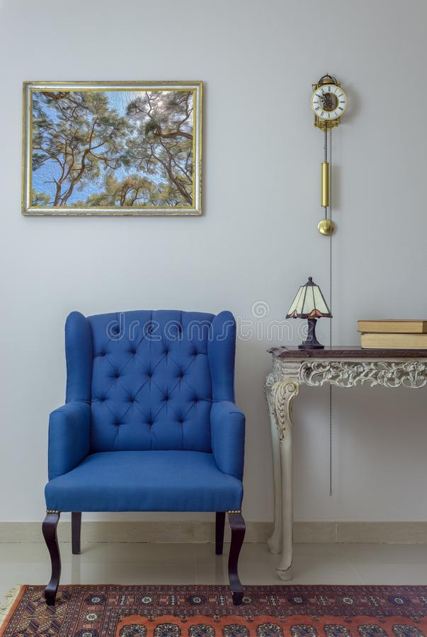 Interior composition of retro blue armchair, vintage wooden beige table, table lamp, books, and pendulum clock over off white wall stock photos