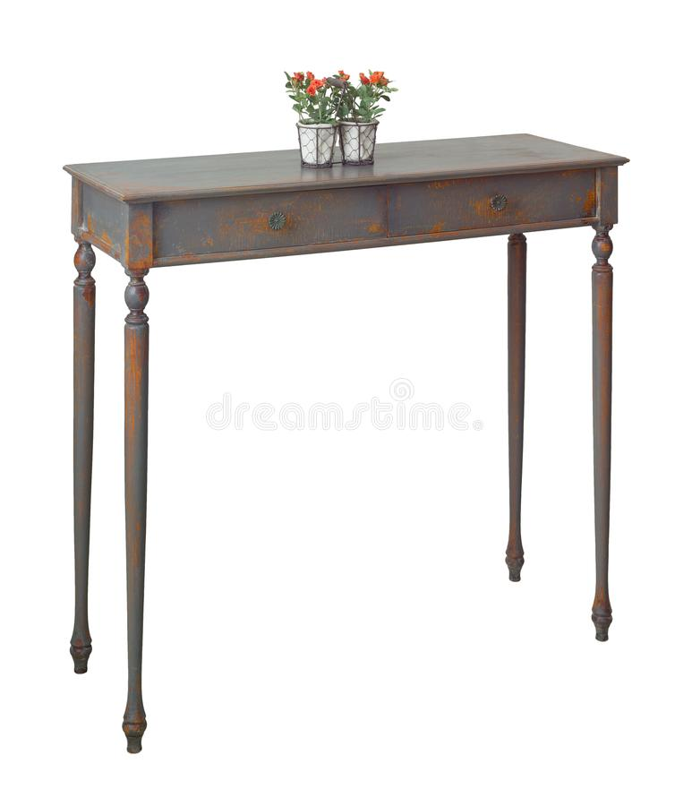 Old style desktop planter with red flowers on the top of retro wooden vintage table with two drawers painted in grey and orange stock photo