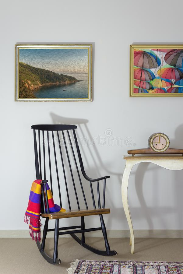 Vintage Furniture: Rocking chair and antique desktop clock on old style vintage table on background of off white wall royalty free stock images