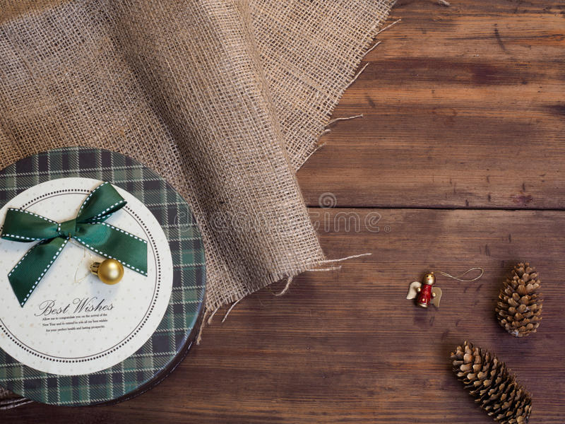Vintage gift box, fir cones, Christmas toy on wood and burlap background, photo top view. Copy space for text. Vintage gift box, fir cones, Christmas toy on stock image
