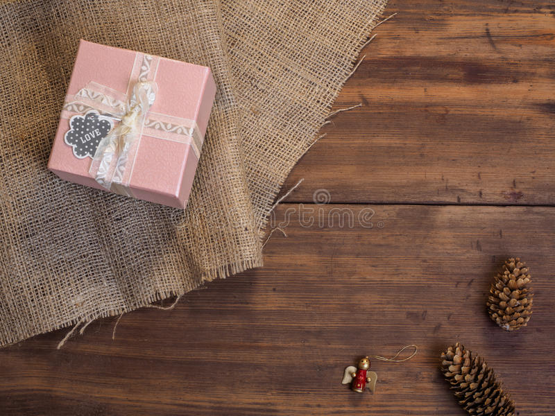 Vintage gift box, fir cones, Christmas toy on wood and burlap background, photo top view. Copy space for text. Vintage gift box, fir cones, Christmas toy on stock images