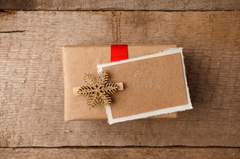Vintage gift box package with blank gift tag on old wooden background. Christmas festive close up, copy space. royalty free stock photos