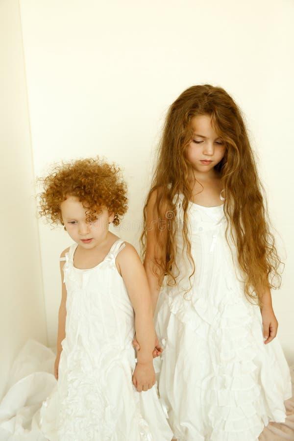 Vintage girls. Little girls in vintage dresses looking down royalty free stock photo