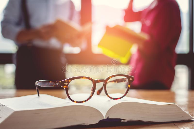 Vintage glasses,on books stack in public library book, Studying examining. Tutor books with friends. Young students campus stock photos