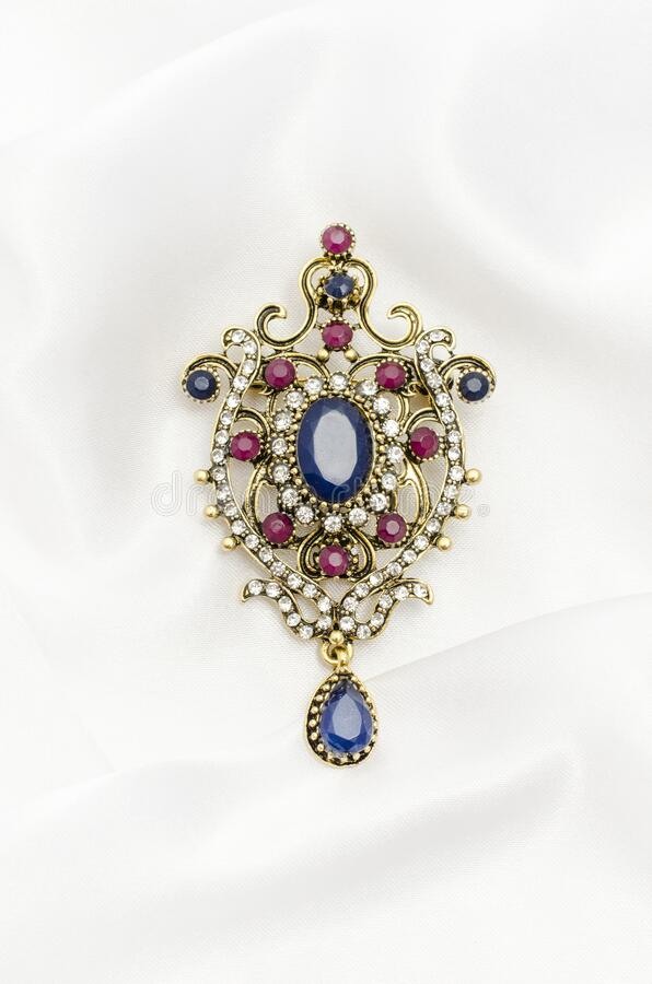 Free Vintage Gold Brooch With Precious Stones On White Silk Royalty Free Stock Photos - 206747428