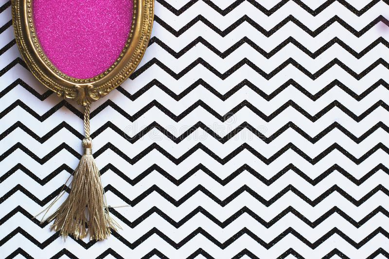 Golden oval picture frame on black and white chevron background, with copy space in the frame royalty free stock photography