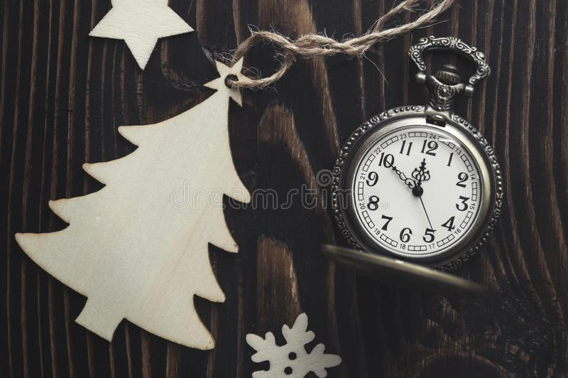 Vintage golden pocket watch and wooden Christmas tree. Concept for New Year or Merry Christmas stock images