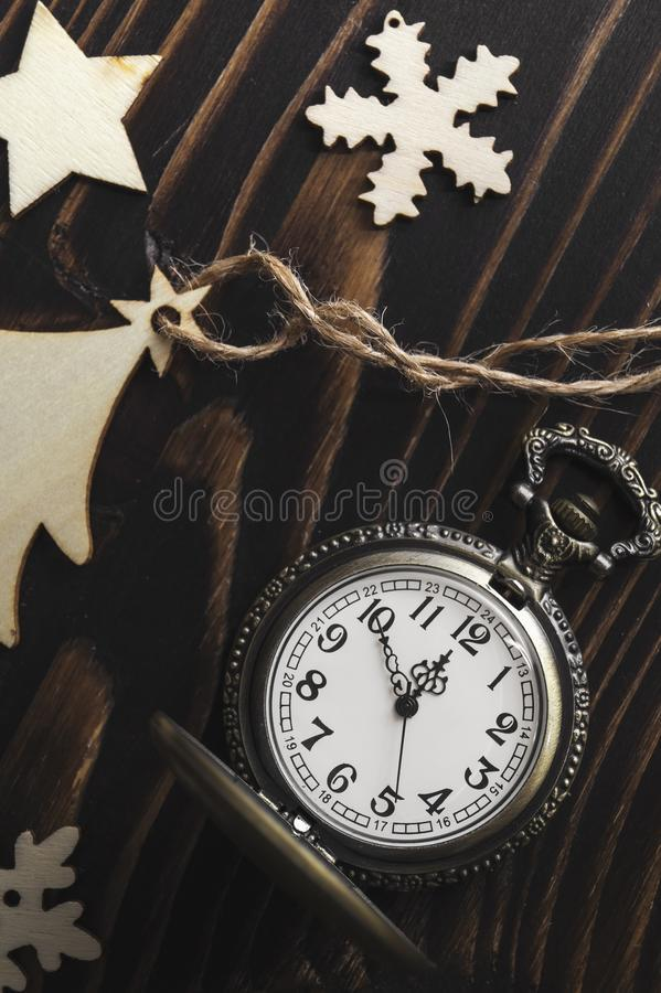 Vintage golden pocket watch and wooden new year  decoration. Close up royalty free stock photo