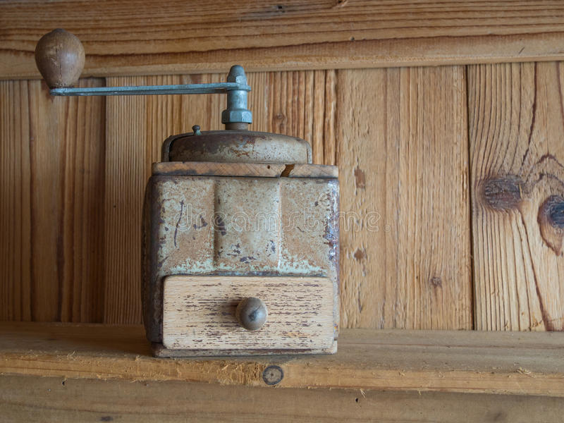 Vintage hand cranck coffee grinder, wooden boards background stock image