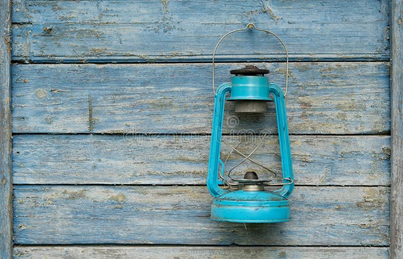 Vintage handle gas lantern on rustic wooden wall. Old fashioned dusty kerosene oil lamp in blue color. Camping light. Interior royalty free stock photography