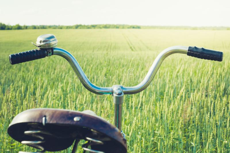 Vintage handlebar with bell on bicycle. Summer day for trip. View of wheat field. Outdoor. Closeup. royalty free stock photography