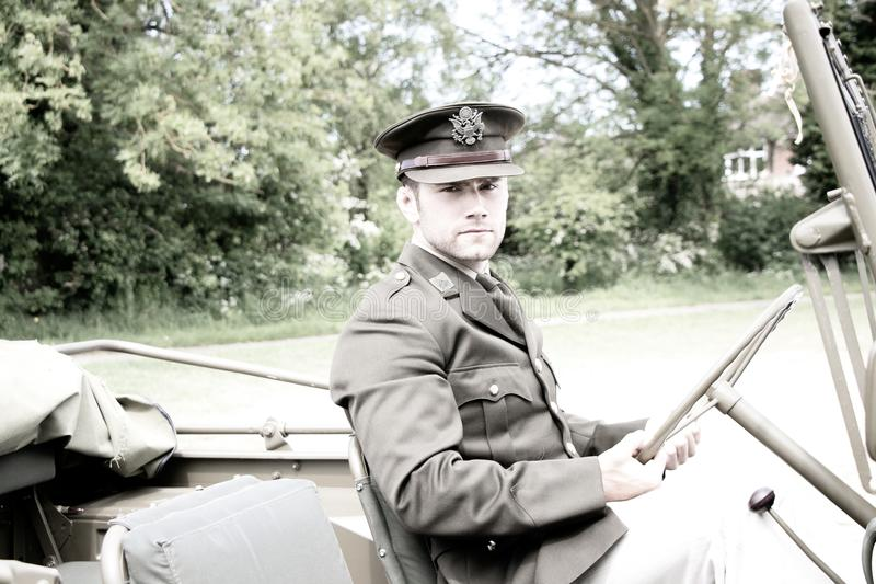 Handsome American WWII GI Army officer in uniform riding Willy Jeep stock photo