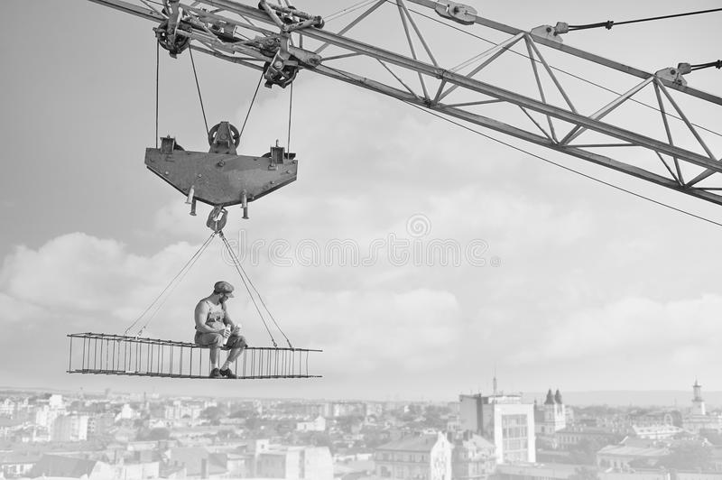 Vintage handyman having lunch on a crossbar hanging above the ci. Perfect lunch. Monochrome shot of a shirtless retro builder enjoying peaceful lunch sitting on stock photography