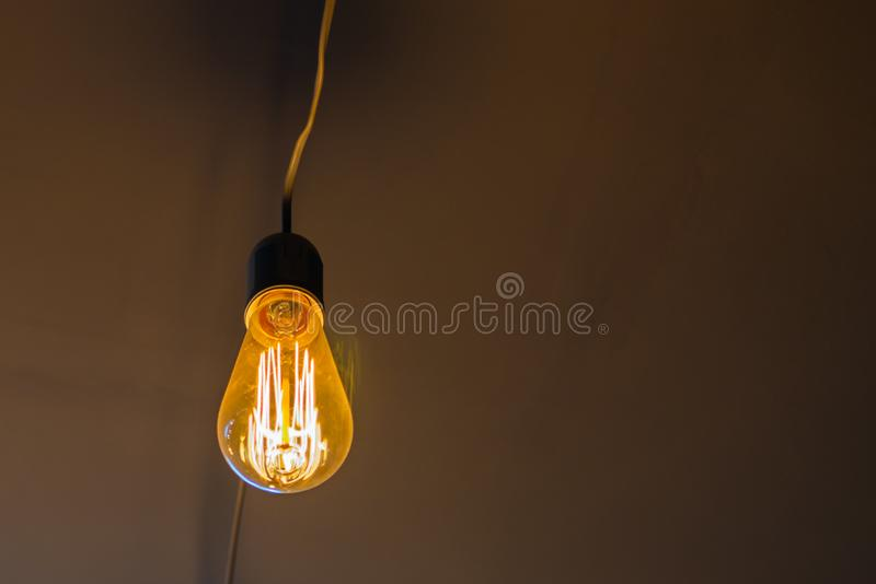 Vintage hanging Edison light bulb over dark background royalty free stock photos