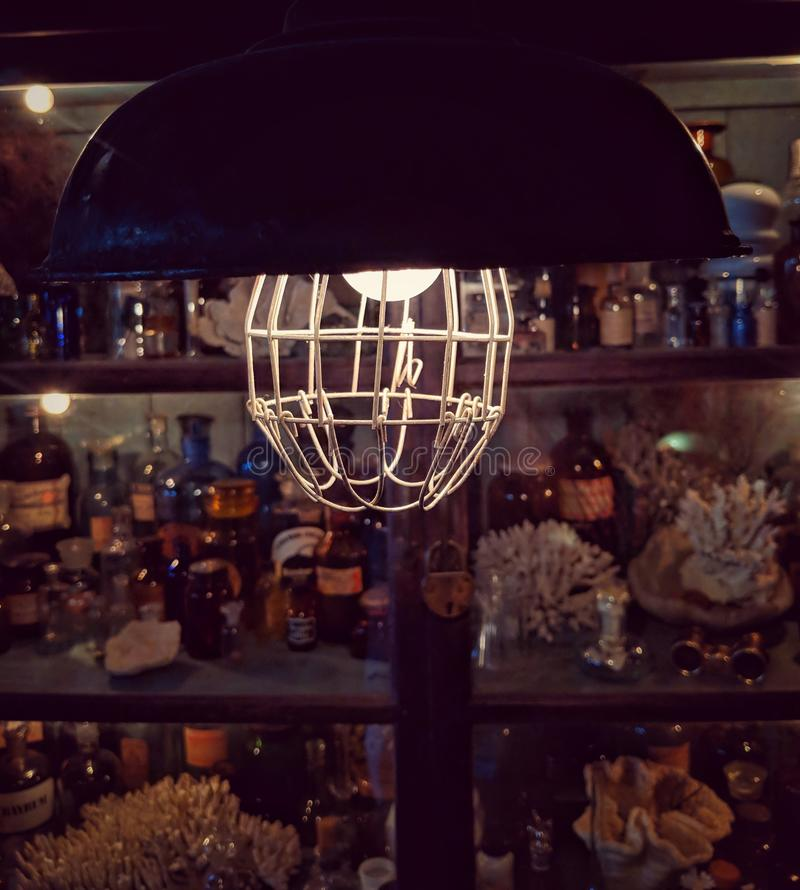 A vintage hanging lamp shining in a dark mysterious room. stock images