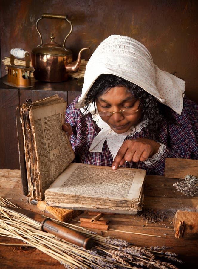 Vintage herb woman reading recipe stock image