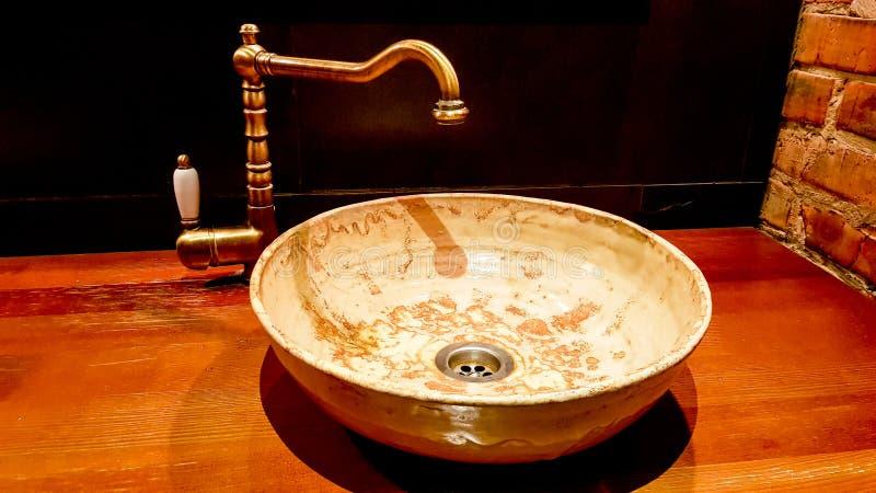 Vintage Hermoso grifo y mezclador dorado golpea un lavabo redondo de mármol en el cuarto de baño. Interior de un baño caro con foto de archivo libre de regalías