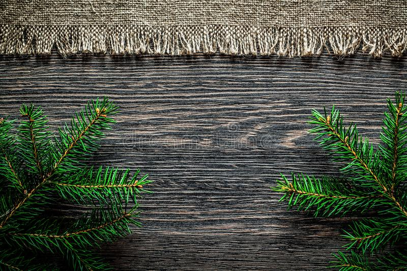 Vintage hessian fir branch on wooden board Christmas background.  royalty free stock photos