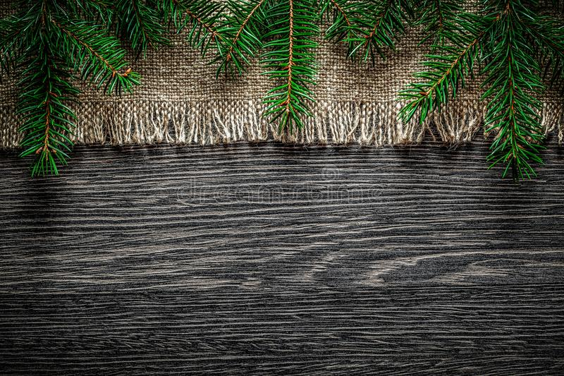 Vintage hessian pine branch on wooden board Christmas background.  royalty free stock photography