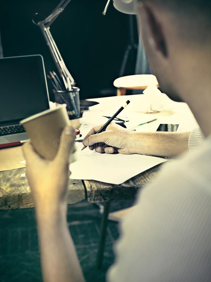 Vintage hipster wooden desktop side view, male hands with cup and holding a pencil stock photo