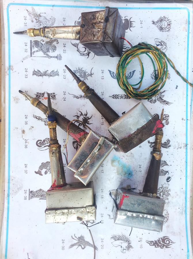 Vintage Home Made Tattoo Guns. A collection of small tattoo guns from a street tattoo artist in India with some of their generic designs to choose from. These stock photography
