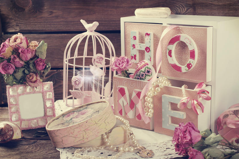 Vintage home still life in romantic style. Vintage home still life with wooden drawers box,pink cage and photo frame in romantic style stock image