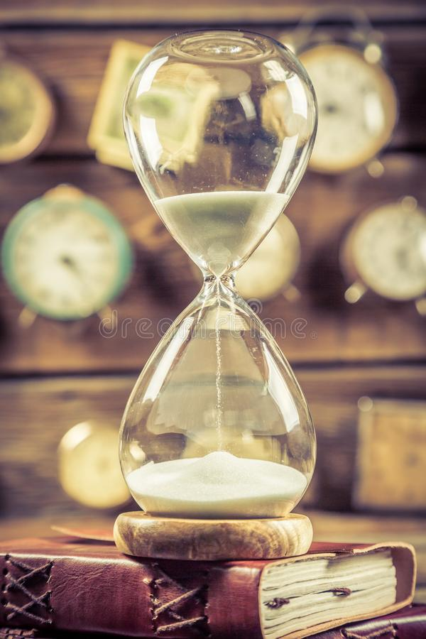 Vintage hourglass on the old books stock photo