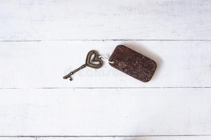 Vintage house key with wooden home keyring on old wood background. Copy space, heart, passion, notebook, text, texture, keychain, property, real, estate, sign royalty free stock images