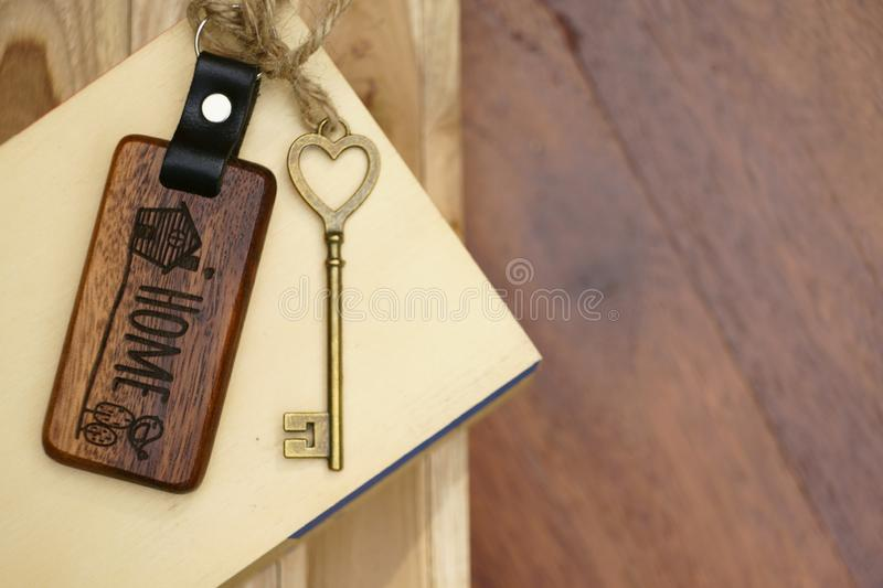 Vintage house key with wooden home keyring on wood board background, property concept, copy space. Vintage house key with classic wooden home keyring on wood royalty free stock photo