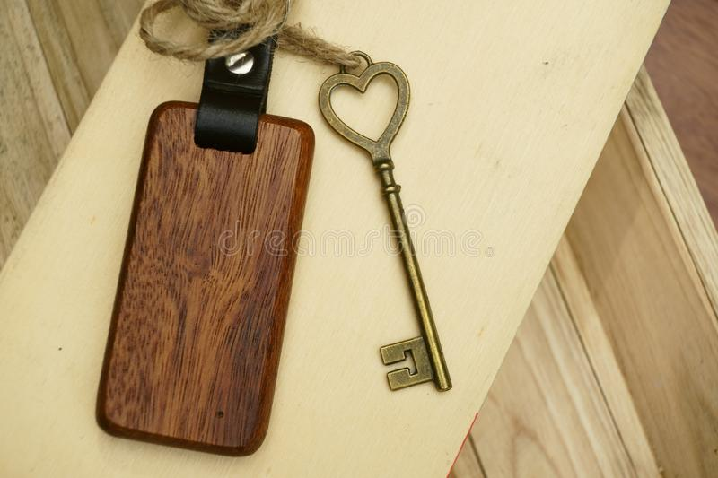 Vintage house key with wooden home keyring on wood board background, property concept, copy space. Vintage house key with classic wooden home keyring on wood stock photo