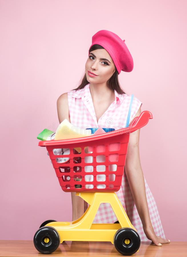 Vintage housewife woman ready to pay in supermarket. retro woman go shopping with full cart. happy parisian girl. Enjoying online shopping. savings on purchases royalty free stock photos