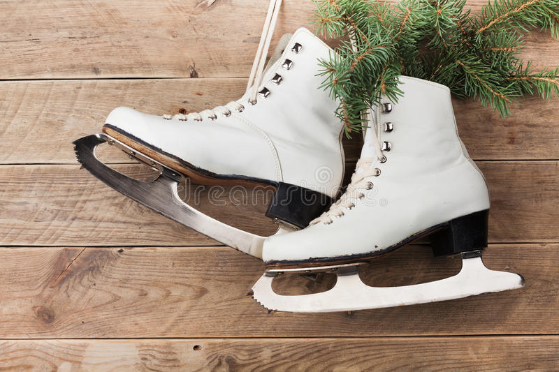 Vintage ice skates for figure skating with fir tree branch hanging on rustic background. Christmas decoration. royalty free stock photos