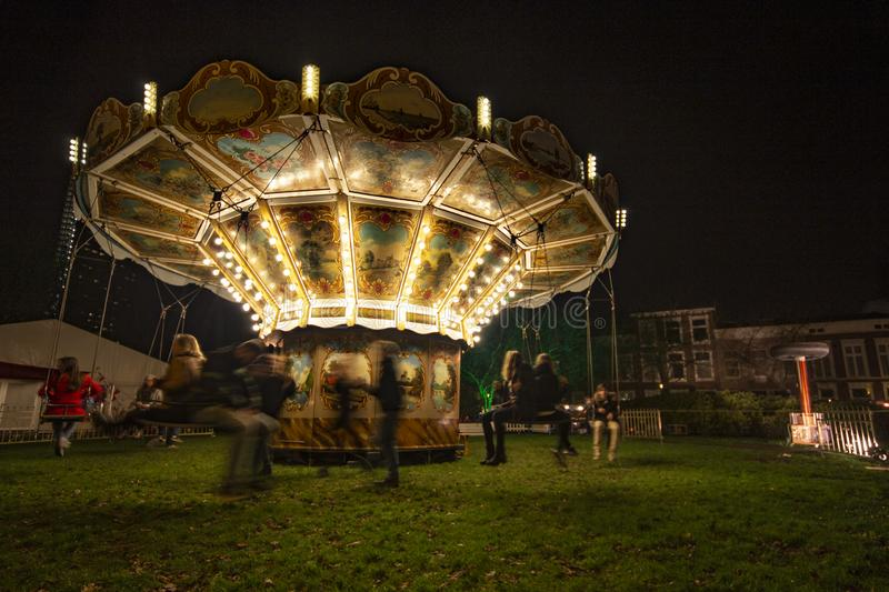 Vintage illuminated Merry-go-round. Children enjoying the carousel, vintage illuminated merry-go-round at night during the light festival in Delft market place stock image