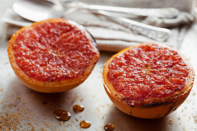 Vintage image of broiled grapefruit with brown sugar and cinnamon on metal surface, healthy dessert is good for breakfast royalty free stock image