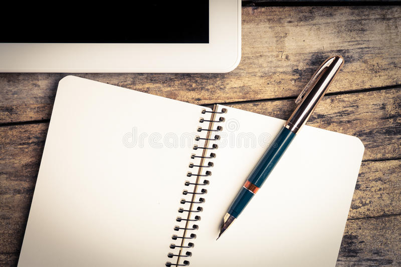 Vintage image of digital pad and old fountain pen with notebook royalty free stock photography