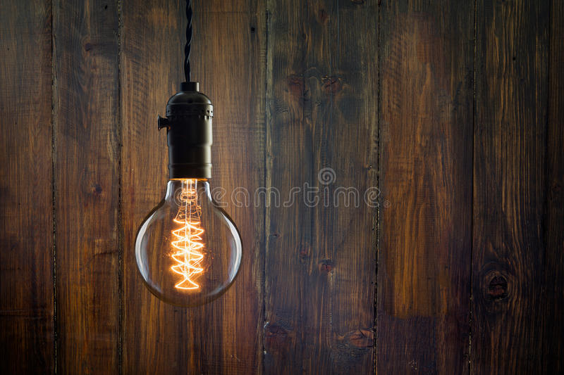 Vintage incandescent Edison type bulb on wooden background. Vintage incandescent Edison type bulb on wooden wall royalty free stock photography