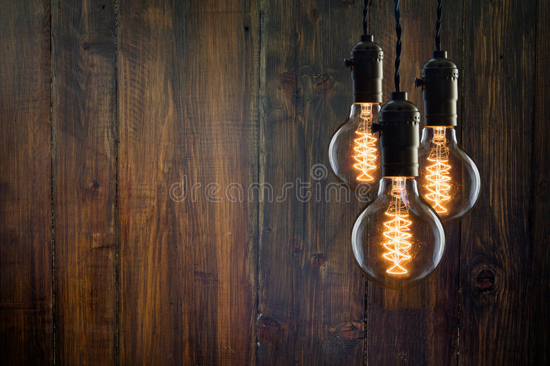 Vintage incandescent Edison type bulbs on wooden background. Vintage incandescent Edison type bulbs on wooden wall royalty free stock photos