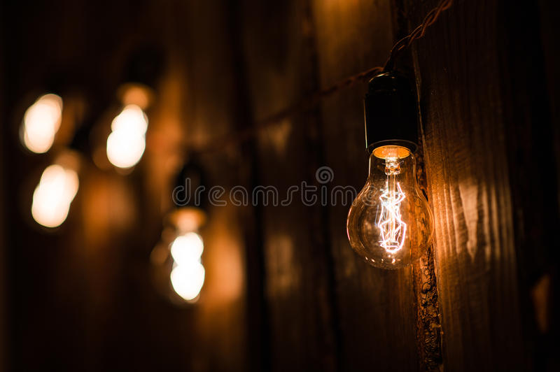 Vintage incandescent Edison type bulbs on wooden wall.  royalty free stock photo