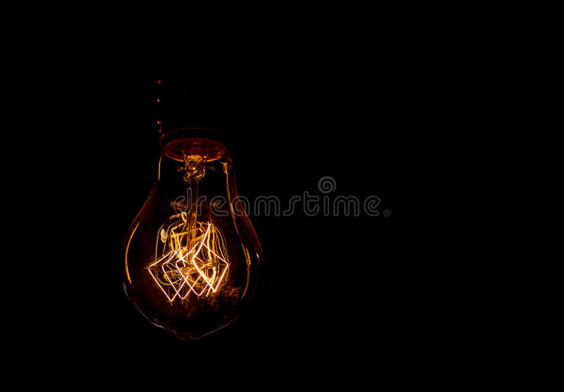 Vintage incandescent light bulb filament on black. Close up shot stock photo