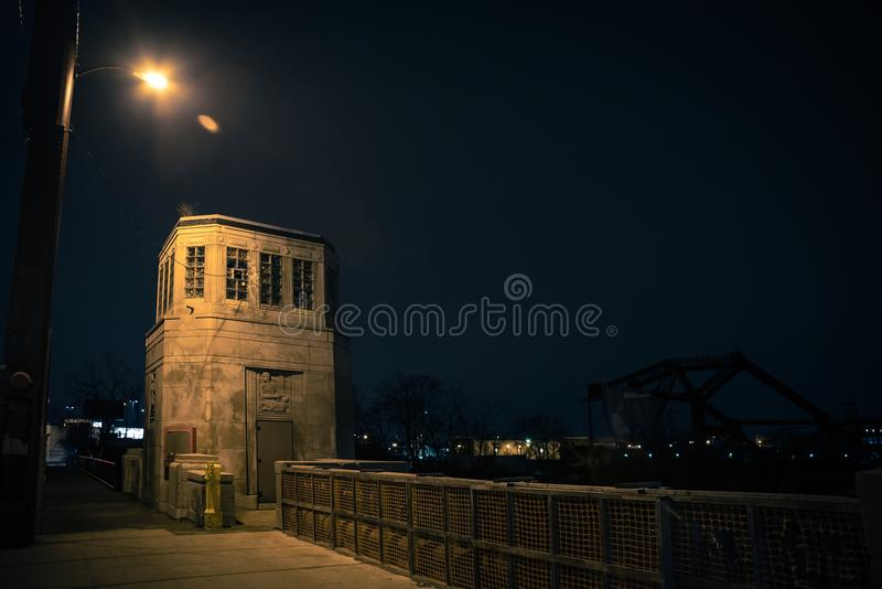 Vintage industrial city bridge with tower house at night. Vintage industrial city bridge with tower house and urban sidewalk at night royalty free stock photo