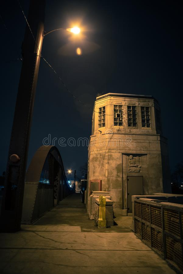 Vintage industrial city bridge with tower house at night. Vintage industrial city bridge with tower house and urban sidewalk at night stock images