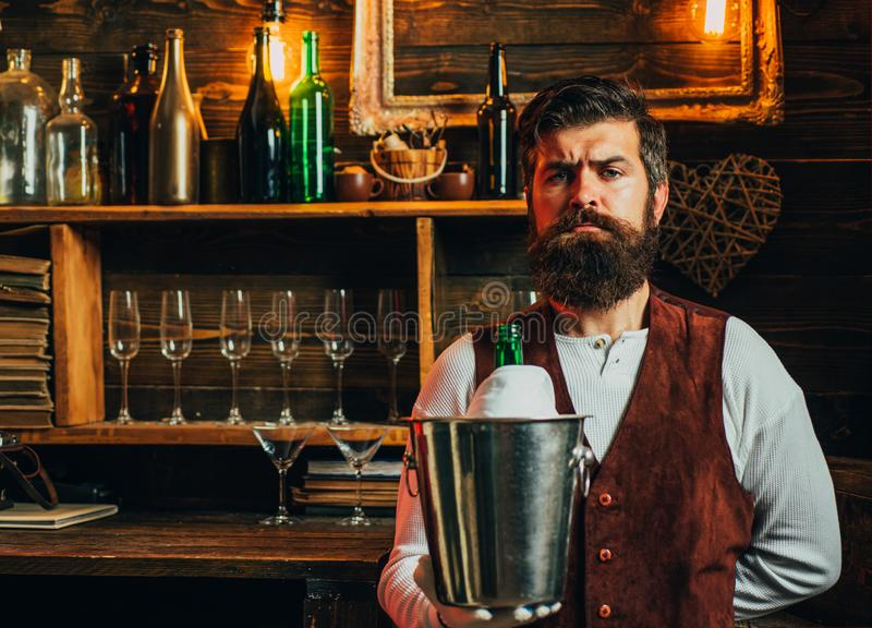 Vintage interior. Hipster male with stylish beard and hair. Elegant hipster with bearded face. Bearded bartender or. Waiter in work uniform. Hipster stock photo