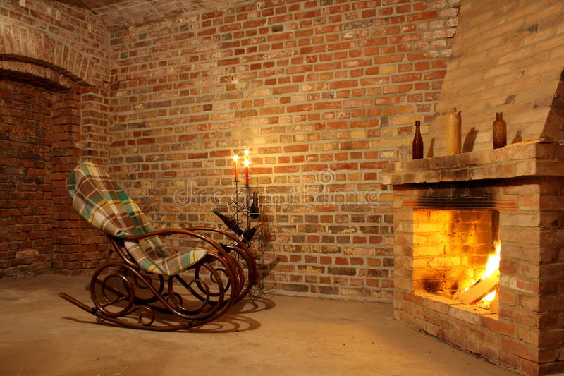 Vintage interior with rocking chair by fireplace and candles