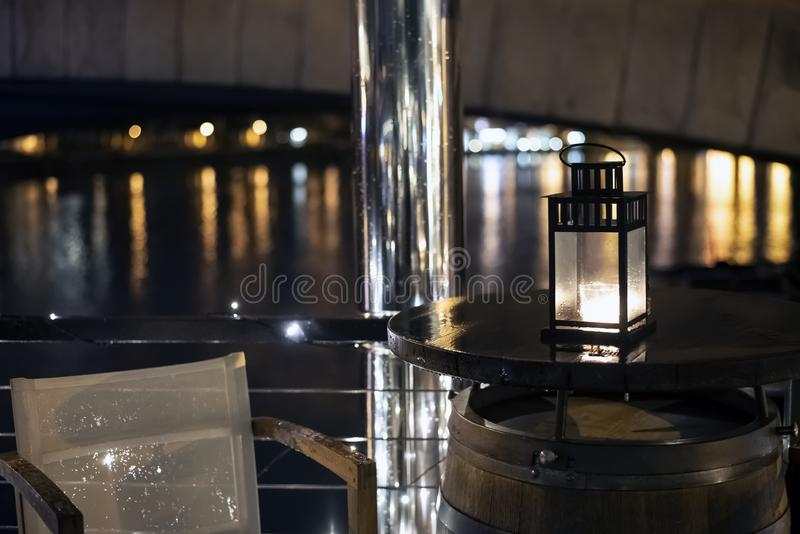 Vintage iron christmas lantern with burning candle light. On wooden table barrel on restaurant terrace on water in Prague royalty free stock photo