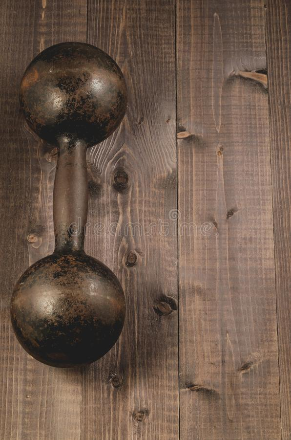 vintage iron dumbbell on the black wooden background/vintage iron dumbbell on the black wooden background, top view and copyspce stock photo