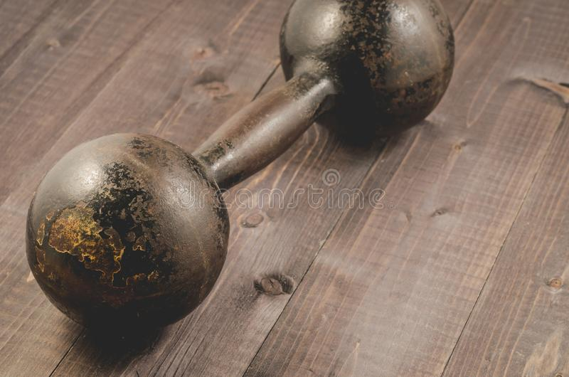 Vintage iron dumbbell on the black wooden floor/iron dumbbell in fitness gym on a dark wooden floor. Copy space royalty free stock photos