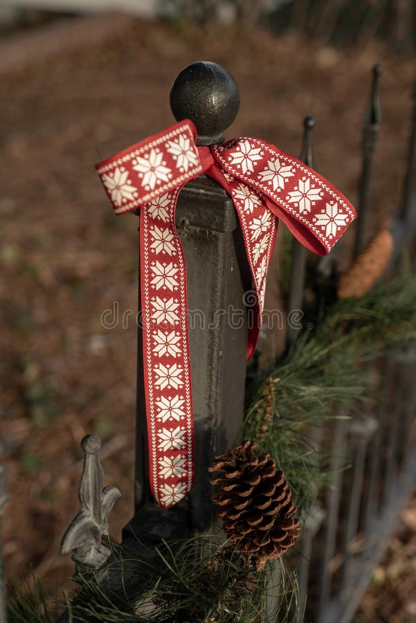 Vintage iron fence pine tree garland,pine cone, red ribbon decoration royalty free stock photography