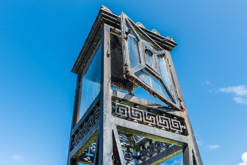 Vintage iron lantern tower with glass doors and stand isolated o. N blue sky stock photography